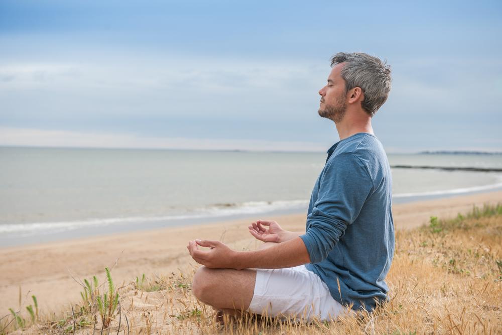 Mann erlernt am Strand zu meditieren