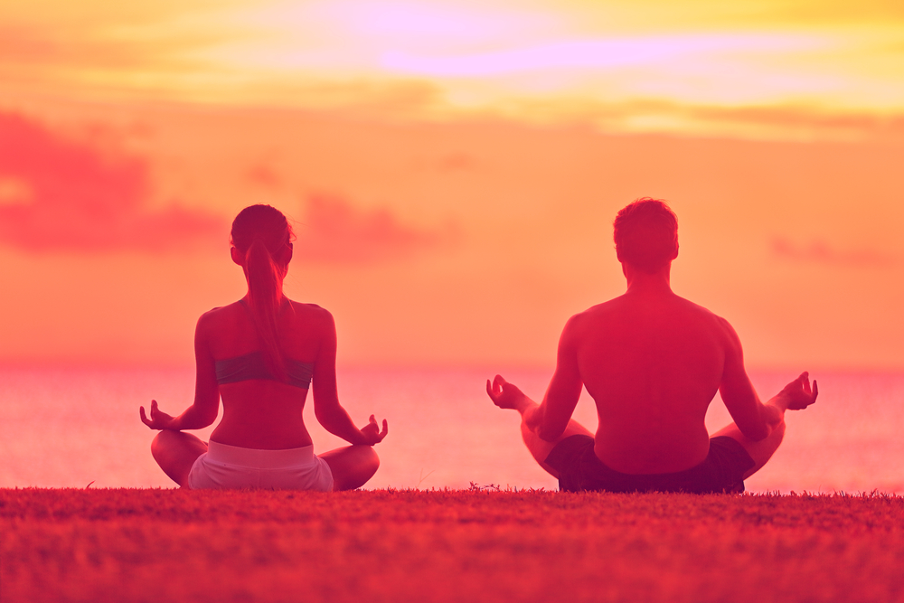 Meditation mit dem Partner bei Sonnenuntergang am Strand