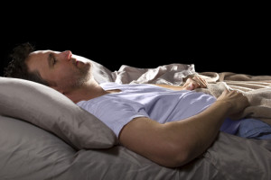 Mann meditiert vor dem Schlaf