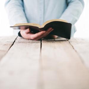 Mann hält Bibel und meditiert