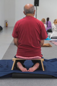 Mann meditiert auf Meditationsbank